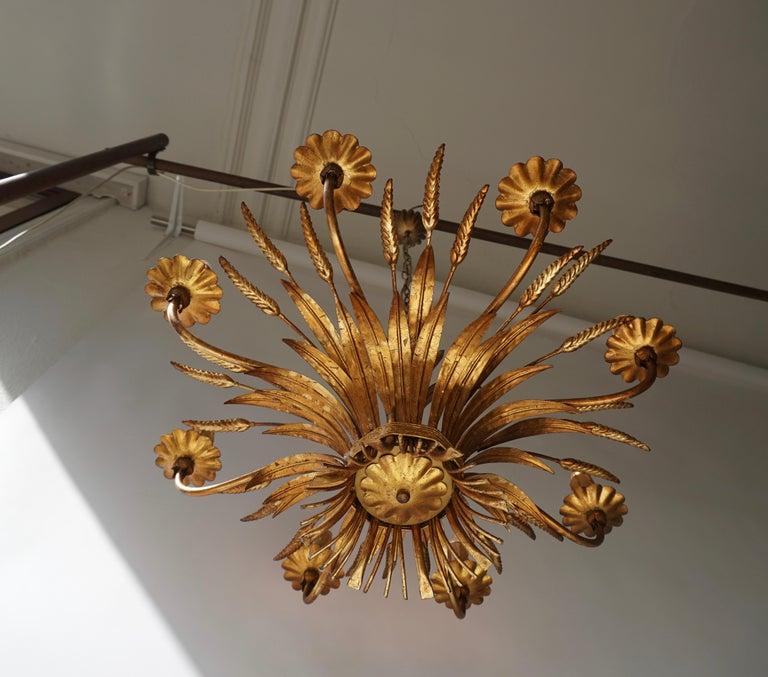 1970s gilt palm leaf chandelier.  The light requires eight single E14 screw fit lightbulbs (60Watt max.) LED compatible. Measures: Diameter 67 cm. Height fixture 45 cm. Total height 110 cm.