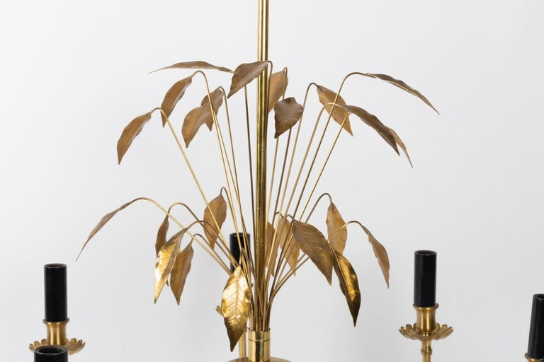This elegant chandelier, entirely made of gilded brass, has 8 luminous arms. It is decorated in its upper part with a bouquet of laurel leaves carefully drawn. Whimsical work of the House Charles designed and realized in the 1970s. In perfect