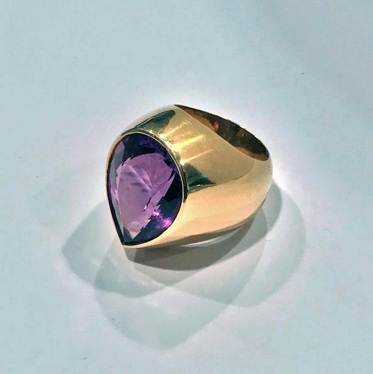 1970's 18K Amethyst large Ring. The Ring set with a fine purple heart shaped amethyst gauging approximately 21.00 x 16.00 x 10.04 mm, approximately 17 cts, plain wide tapered custom mount and shank. Stamped Aarhus on interior of shank and maker's