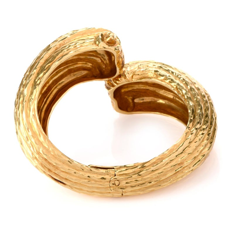 This incredible late 1970's 18K gold  cuff Bangle Bracelet was inspired in shell motif.  The ribbing of the shell design boasts a high polished hammered effect creating depth and interest.  The center of the vintage Bracelet is hinged for ease in