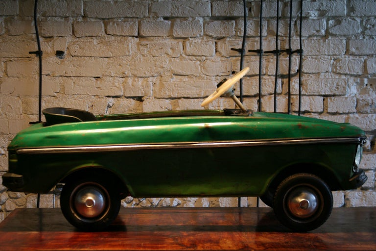 A metal children's pedal car from the 1970s of the Soviet production. It is a model which is the successor of Volga car, popular in the 1960s.  Construction : The body is made of pressed welded sheet. The drive is on the  rear axle, rubber tires,