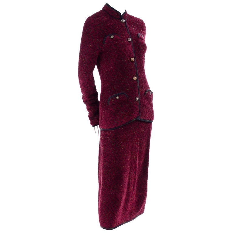 This is a very stylish Adolfo burgundy red skirt suit with a subtle black and green zig zag pattern in the gorgeous knit fabric with black trim. The long jacket has a mandarin collar and 4 decorative inverted flap pockets with lions head brass