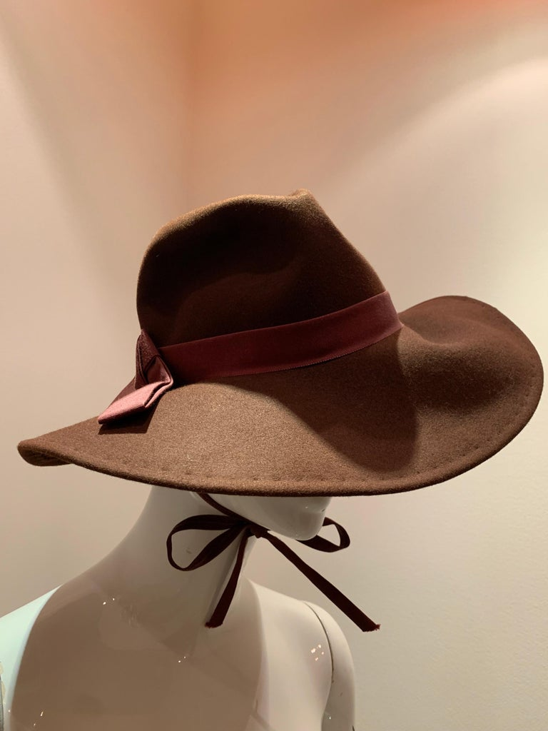 A handsome 1970s Adolfo wide brimmed menswear-styled chocolate brown wool felt fedora.  Ready for adventure with a chin strap to secure.  Trimmed with grosgrain ribbon band.