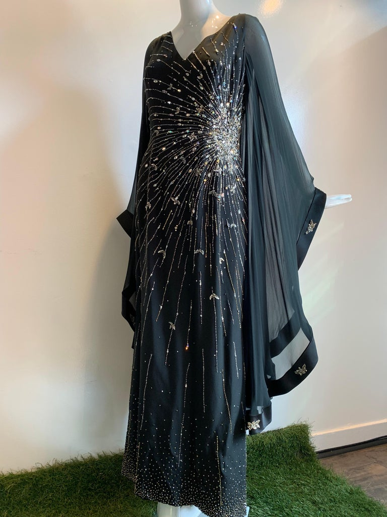 A spectacular 1970s Alan Cherry black silk chiffon Goddess-style evening gown with a huge starburst of star-shine across the body from hip to bust in beadwork and rhinestones.  Sleeves are angel-wing style edged in silk satin with beaded medallions.