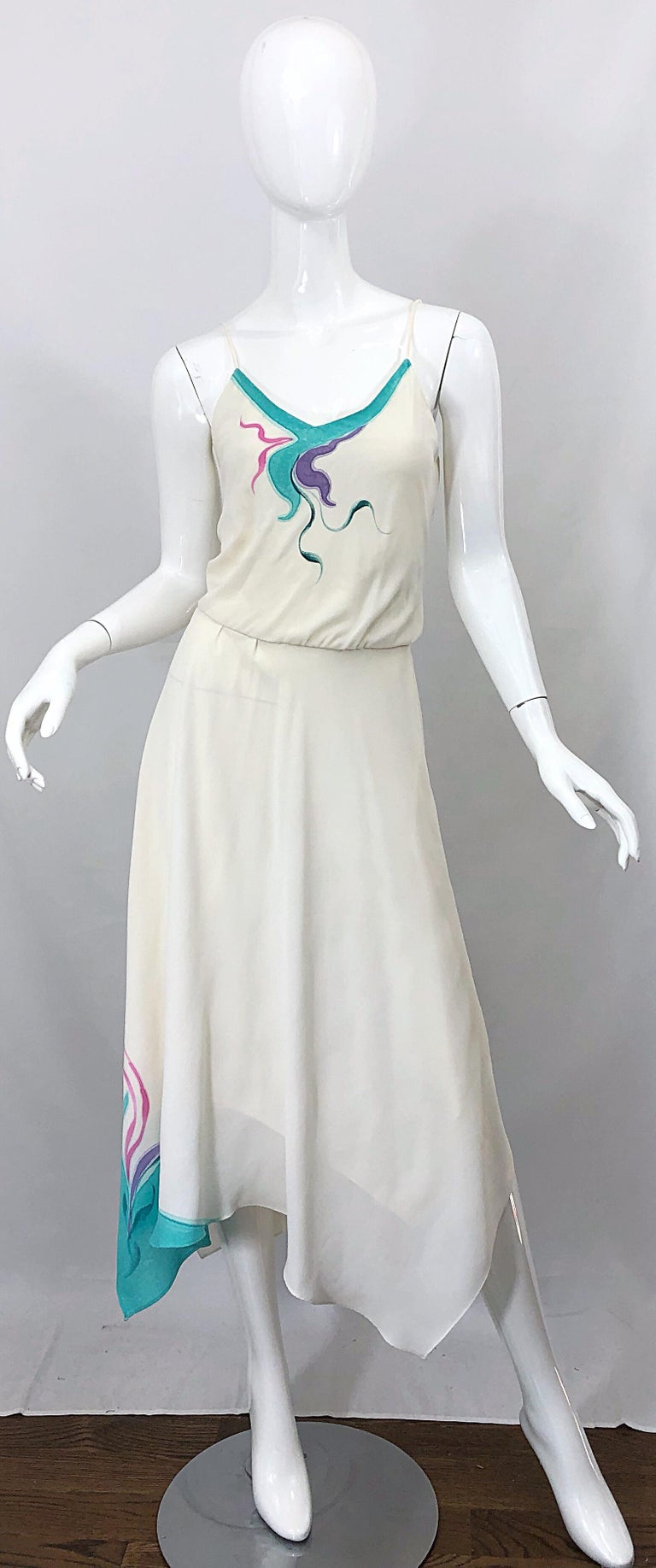 Amazing late 1970s handkerchief hem ivory, turquoise blue, pink and purple swirl print dress! Features a swirl screenprint on the bodice and on the right side of the hem of the skirt. Elastic waistband can stretch to fit an array of sizes. Great for