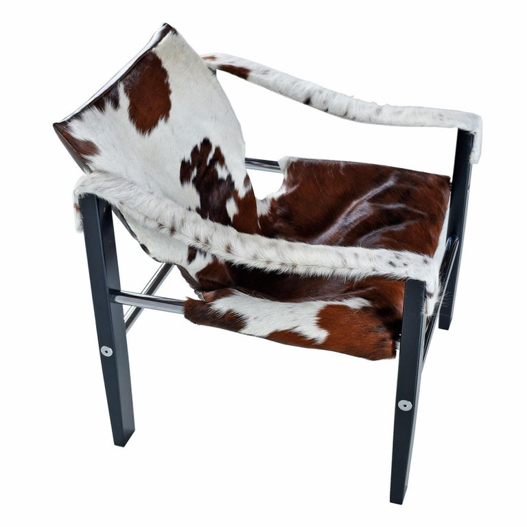 Our restoration team has raised the bar for the Safari Chair. Not only did we go with new, authentic cowhide leather, but the frame has been repainted to match the original black satin finish. The fuzzy hide arm slings finish off the look and help