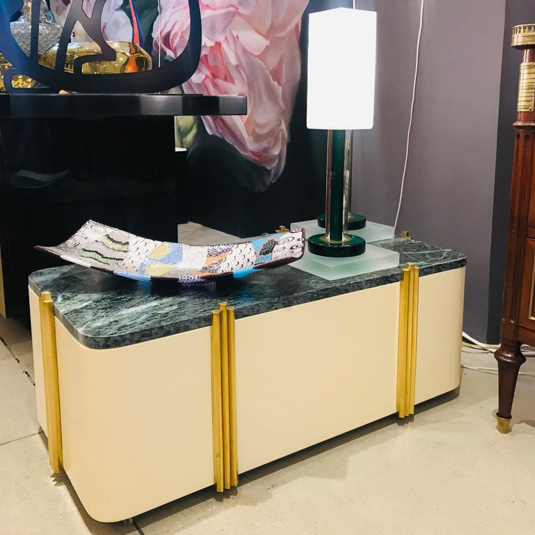 A very interesting and rare Italian modern sofa table on brass casters, of Art Deco design, entirely handcrafted in ivory white lacquered wood topped with green Italian Verde Issorie marble, elegantly decorated on each side with vertical brass