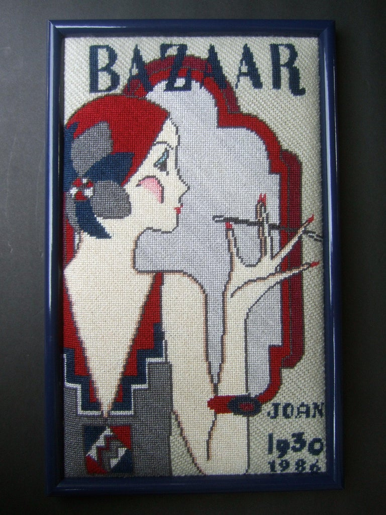 1970s Art Deco Inspired framed artisan needlepoint wall hanging  The hand-stitched artisan scene features an elegantly dressed 1930s  era woman gazing into a needlepoint stitched faux mirror  The Bazaar caption replicates a vintage 1930s era