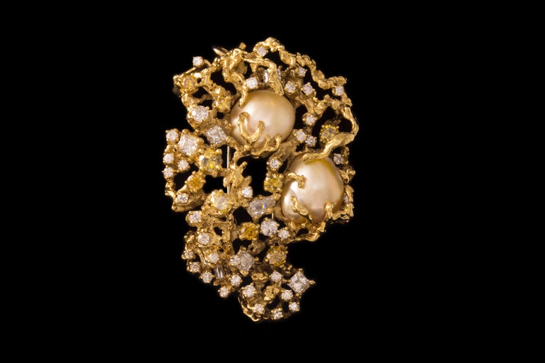 A baroque south sea pearl, white and colored diamonds, and 18 karat gold brooch/pendant, by Arthur King, 1970s. The brooch measures 2.56