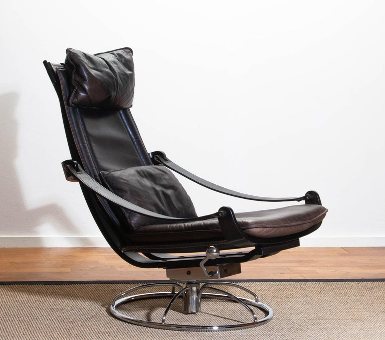 Extremely beautiful and artistic swivel and relaxing easy / lounge chair designed by Åke Fribytter for Nelo Sweden.  This high quality chair features a plywood frame and Brown leather cushions and a chromed metal base. The armrests are made of