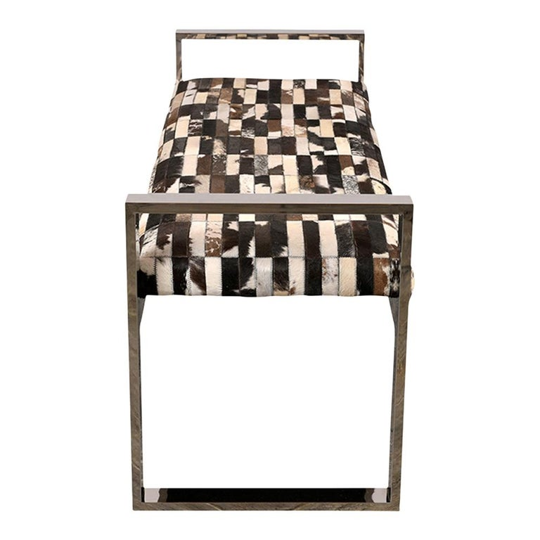 Modern Aspen bench with a square, polished chrome frame. The seat features a mix of cowhide patterns all topstitched together. The bench is in good condition ready for any home or office for years to come.