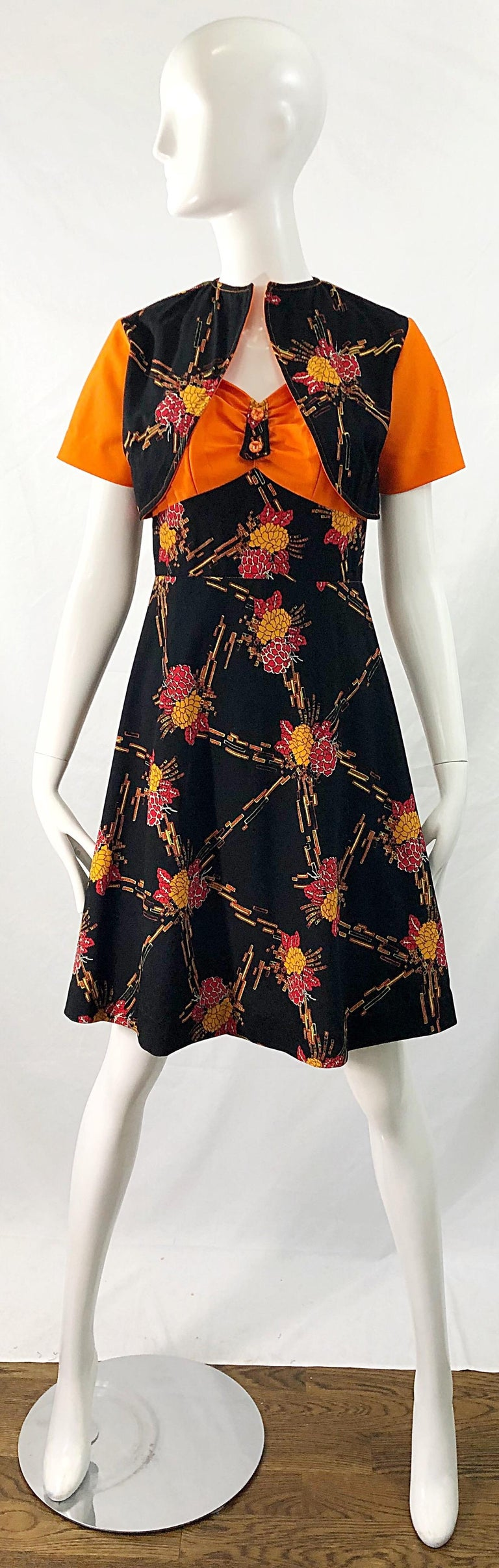 Chic 1970s autumnal colored digital flower printed knit A-Line dress and cropped bolero jacket ! Perfect for Halloween ! Warm vibrant colors of orange, marigold, red and white on a black backdrop. Hidden zipper up the back with hook-and-eye closure.