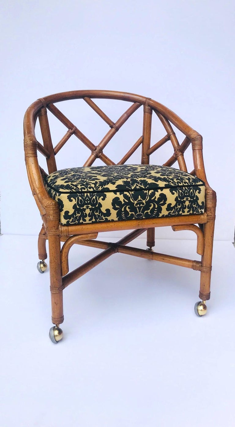 Fabulous Hollywood Regency Chinese Chippendale desk chair. Striking from all angles and easily swivels. Fitted with four brass castors. Upholstered in damask print textile in hues of black over tan, and waterproof.