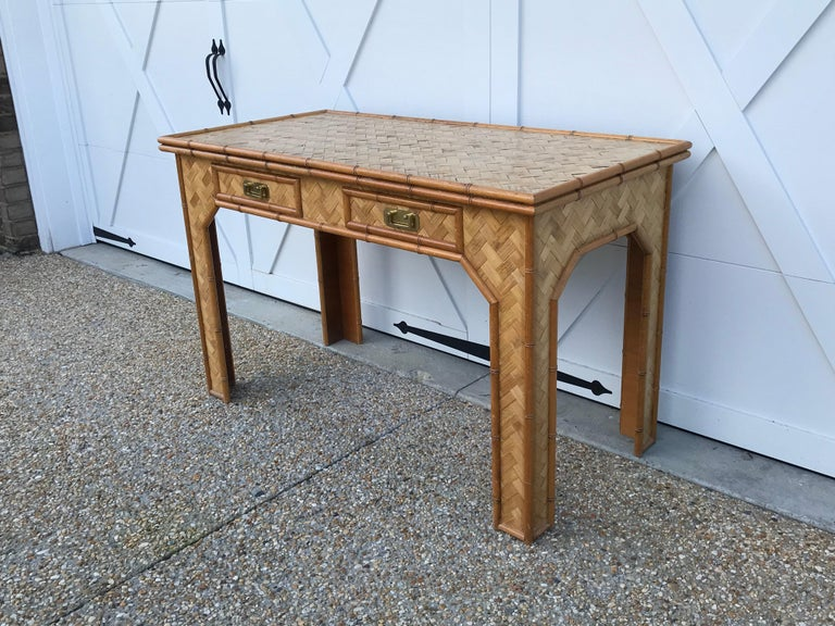 Offered is a stunning, 1970s bamboo writing desk with brass campaign-style hardware. This desk is in great condition and has ample room for working. The two drawers add a sleek storage component. Sturdy and stable, not wobbly. Top has a small lip,