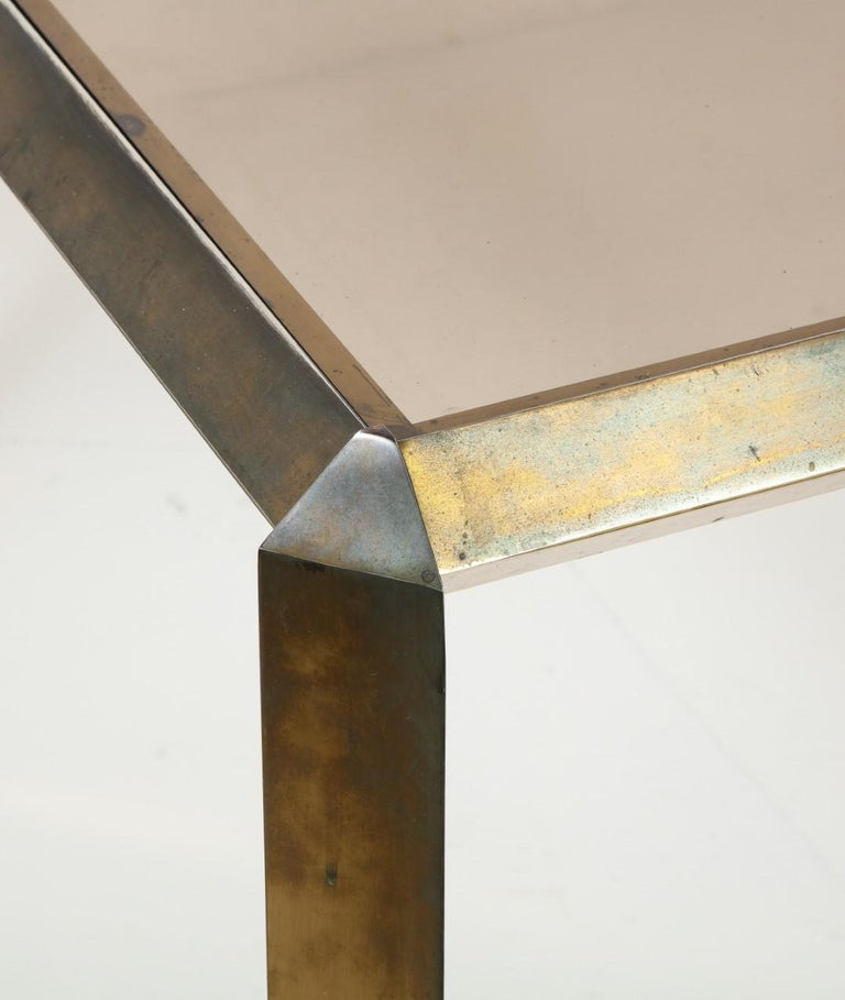 Midcentury 1970s Bauhaus style brass dining table with beveled brass edges around the smoked glass top.