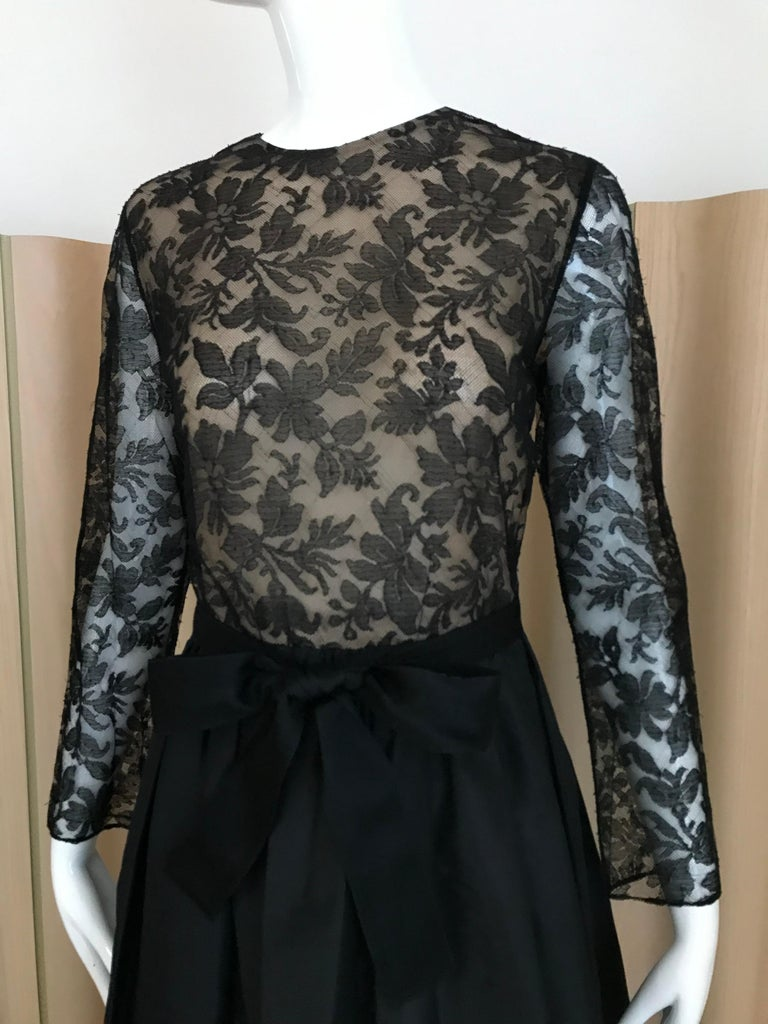 Vintage 1970s Bill Blass Black Lace long sleeve dress with silk taffeta skirt and black ribbon sash. Perfect for black tie event. Size: Medium Bust: 36 inches/ waist: 28 inches/  Dress length: 55inchess / sleeve : 22 inches