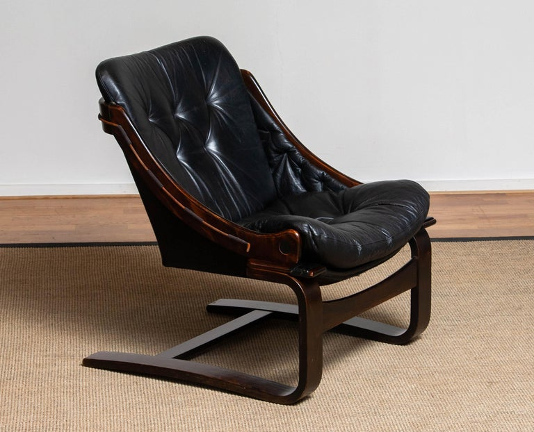 Scandinavian lounge / club chair designed by Ake Fribytter for Nelo Möbel in Sweden.  Upholstered with black leather and dark brown linen. Overall in good condition. Please note that we have two in our gallery!