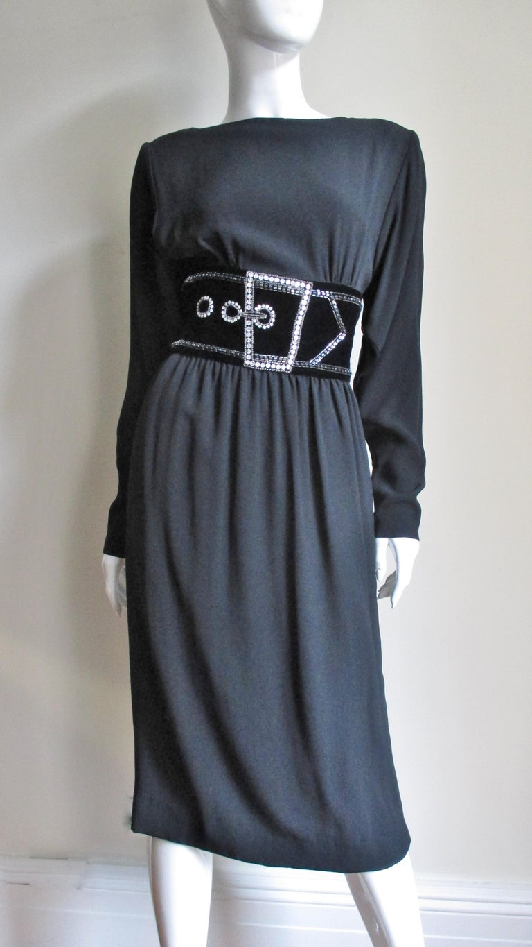 A beautiful black silk dress from Bob Mackie.  It has a front bateau neckline, a square cutout back and sleeves with zippers.  The bodice has light gathering where is attaches to a trompe l'oeil belt comprised of a velvet strip outlined in rows of