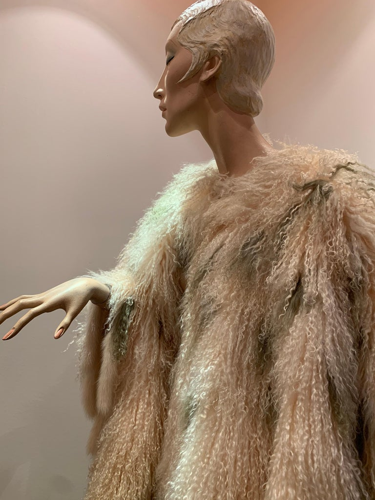 1970s Bohemian Mongolian Lamb Coat Converts To Poncho W/ Mink Tail Fringe. Natural cream color with olive green accents. Satin lined. Maker unknown. Hooks down center front and sleeves.
