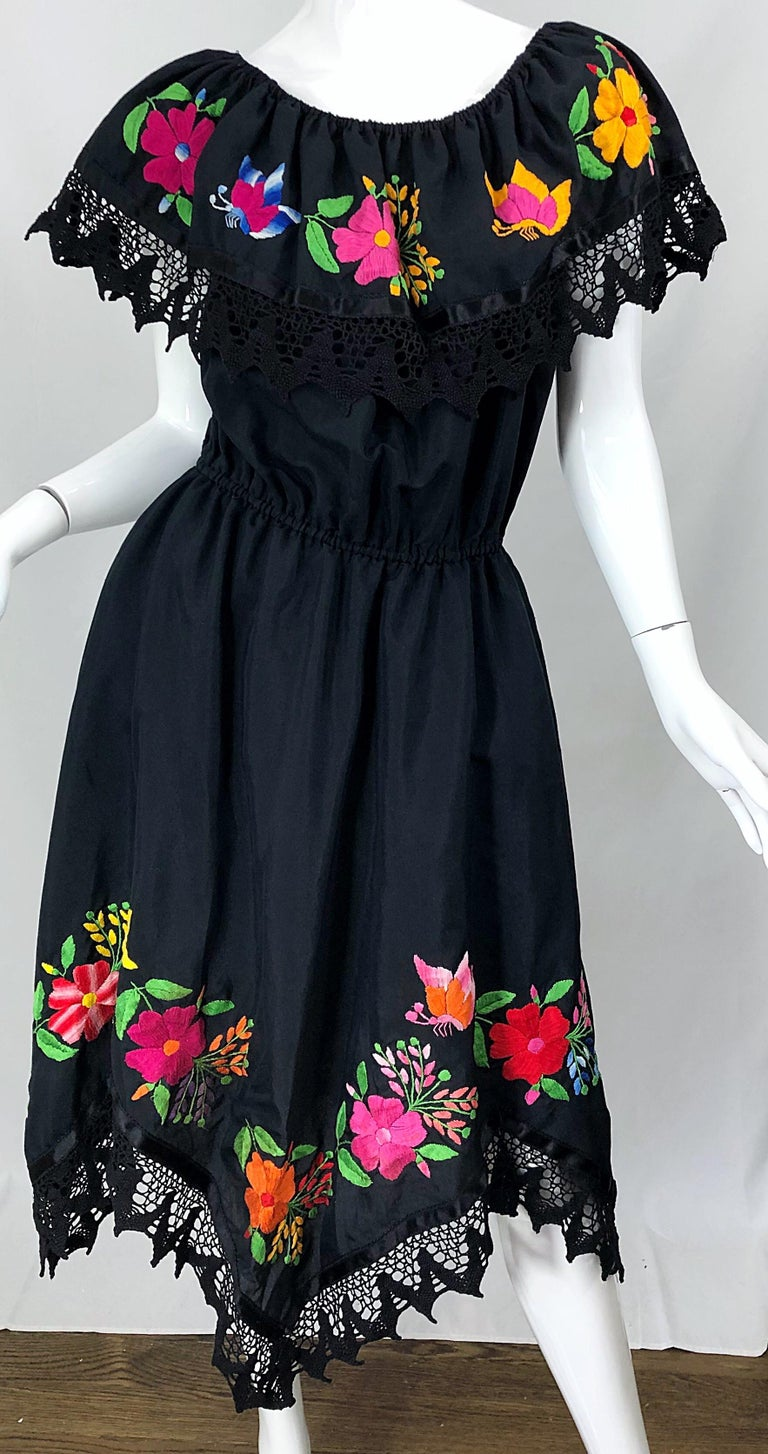 Boho chic 1970s / 70s black cotton embroidered Spanish style dress! The beauty about this dress is that it can be worn two ways, as pictured. It can be worn on or off the shoulders, and looks equally as good either way. Bright flowers in pink,