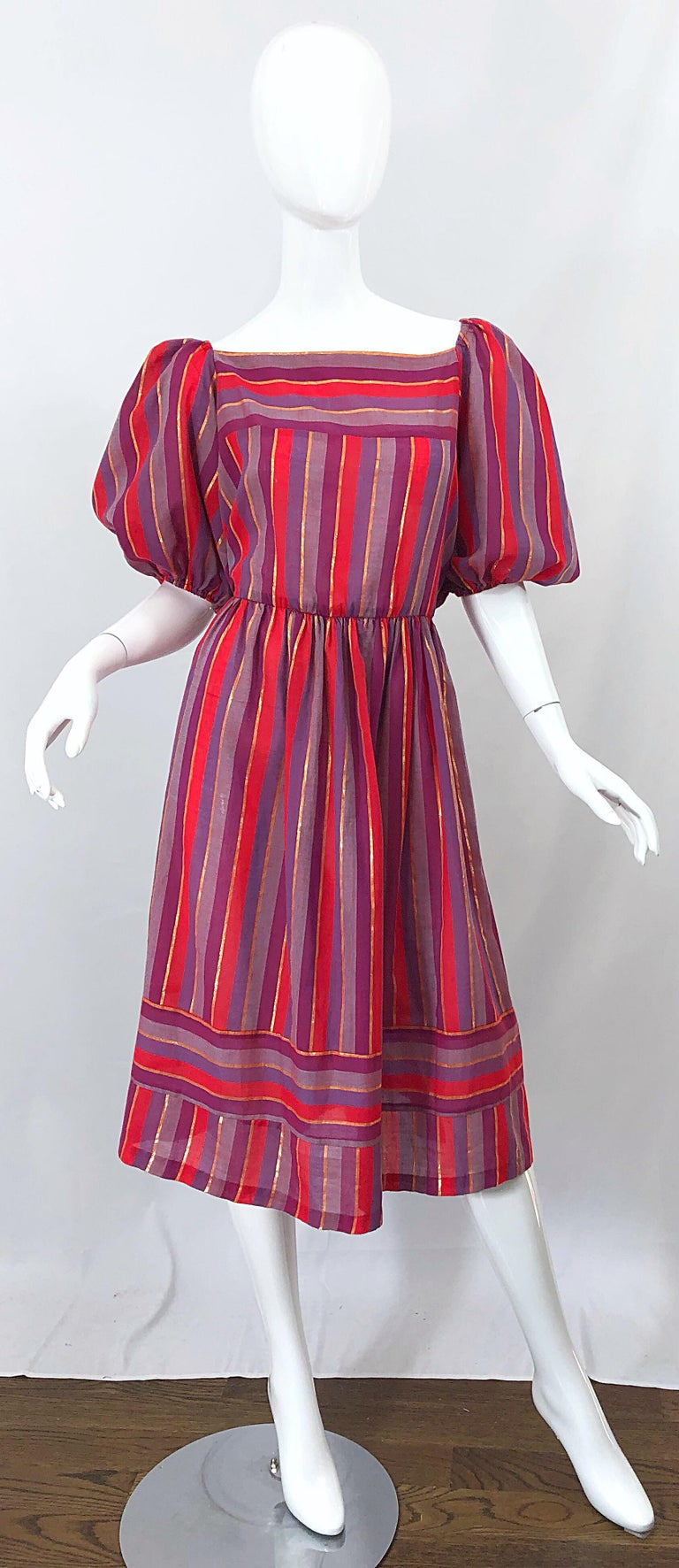 Boho chic 1970s red, purple lilac and metallic gold vertically striped dress! Features chic short puff sleeves. Elastic waistband makes this beauty easy to wear and comfortable. Lightweight cotton voile blend is perfect for any time of year. Hidden