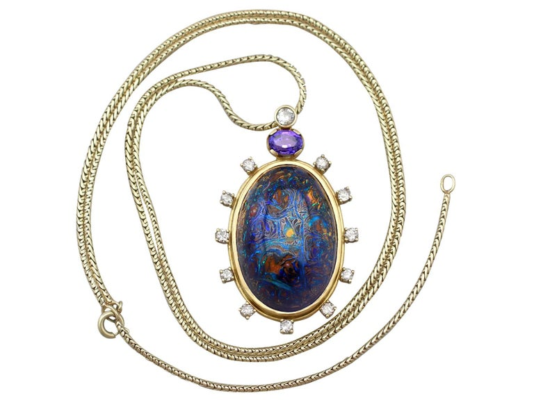 This exceptional and stunning boulder opal pendant has been crafted in 18k yellow gold.  The German-made pendant has an oval form displaying a stunning central cabochon cut boulder opal encircled by a stepped plain 18k yellow gold frame.  The