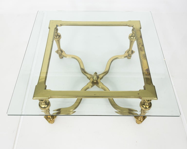 1970s brass and glass English coffee table with glass top. The base is highlighted by trumpet shaped legs and cross stretcher with a center ball finial.