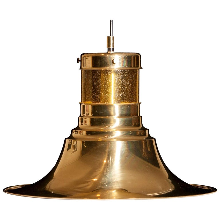 Magnificent pendant designed by Börje Claes for Norellet, Sweden. This lamp is made of brass with an enamel white inside and a yellow cylinder of glass. The beautiful shape makes that it gives a wonderful shining. Period: 1970s. Dimensions: H 32