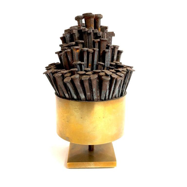 A petite round brass nail sculpture.