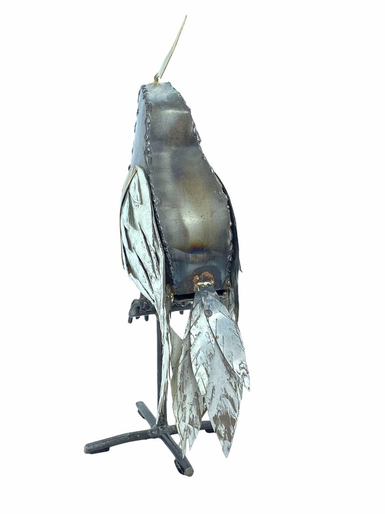 Brutalist parrot sculpture in the style of Sergio Bustamante or Alexander Blazquez.  Handcrafted and welded out of different colored metals. Perched parrot on metal stand. Ideal size for bookcase/etagere styling.Perfect gift idea for the