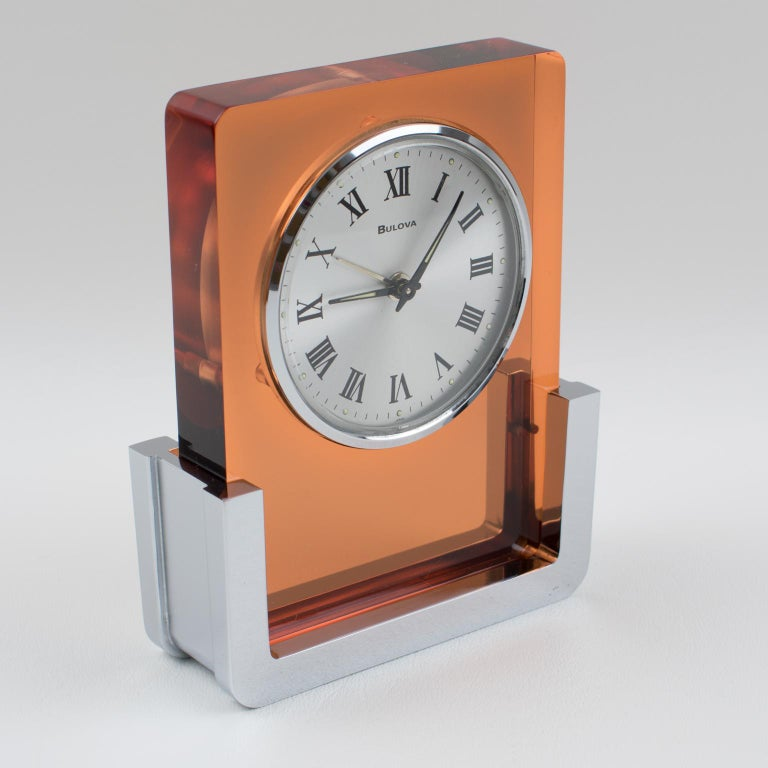 Beautiful modernist table clock by Bulova Japan. Model 2RA007 build with transparent copper Lucite and chromed metal in a very modernist shape. This is a wind up alarm clock, in excellent working condition, it even glow in the dark!! Measurements: