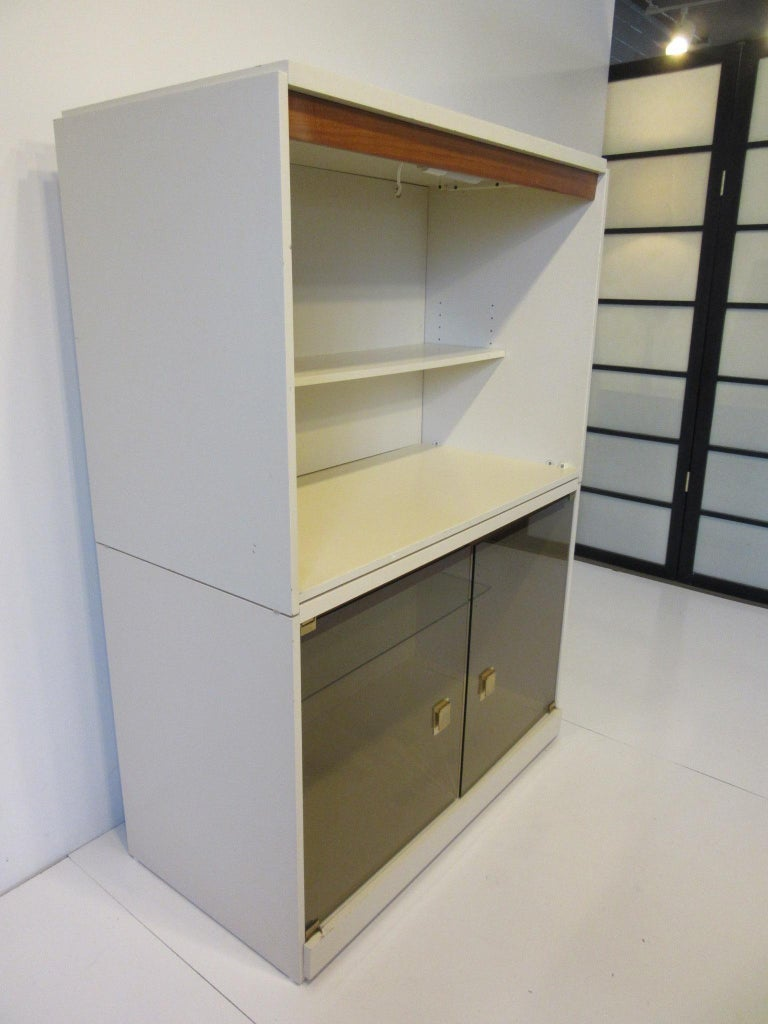 A two-piece cream lacquer finished cabinet or bookcase with adjustable shelves, smoked glass doors, brass pulls, walnut trim and lights to both units. In the manner of Milo Baughman constructed in the 1970s made in Canada.