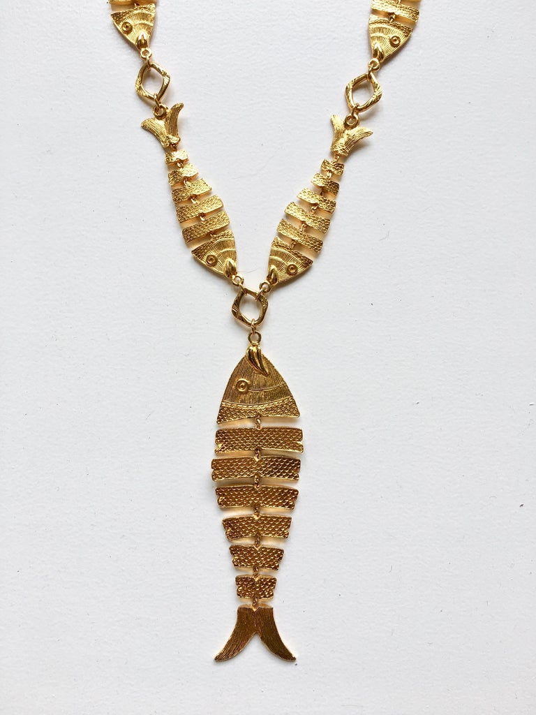 This is a super fun piece made by Cadoro in the 1970s. It features a necklace made up of articulated gold-tone fish with a larger articulated gold-tone fish pendant hanging from it. The necklace without the pendant measures 28 1/2 inches long. The
