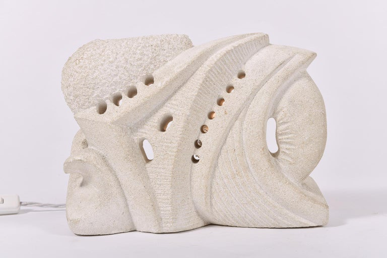 A carved limestone sculptural lamp, of abstract form