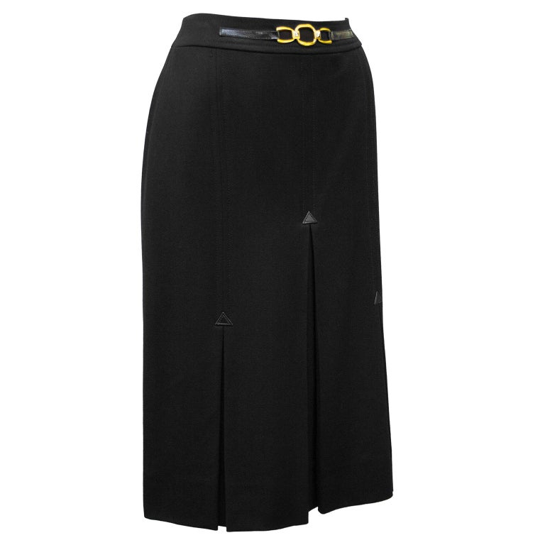 1970's classic Celine black wool gabardine skirt with half black leather and gold belt at waistband. Three inverted stitched box pleats on the front and back with small leather triangle detail. Overall A line shape. In excellent condition, side