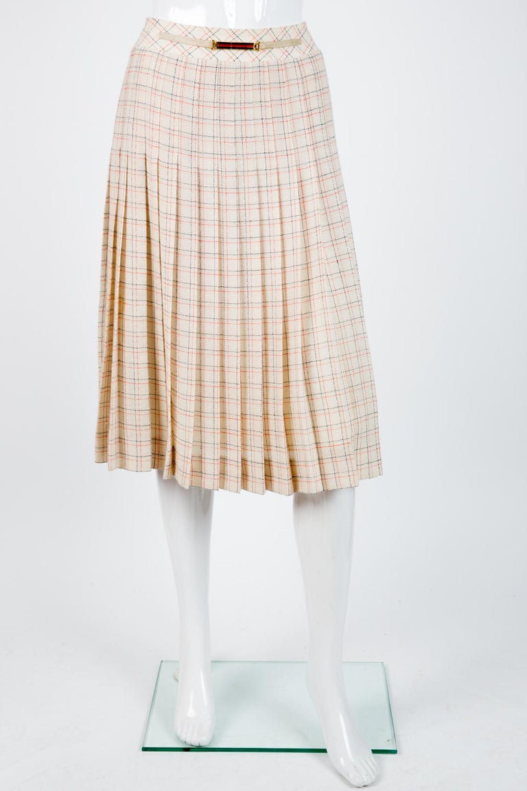 Celine ivory wool skirt featuring a navy and red check pattern, a center back zip, a front leather and music buckle, a logo lining.  80% wool 20% polyamide In excellent vintage condition. Made in France. Label size 38fr/US6 /UK10 but can fit a 36fr/