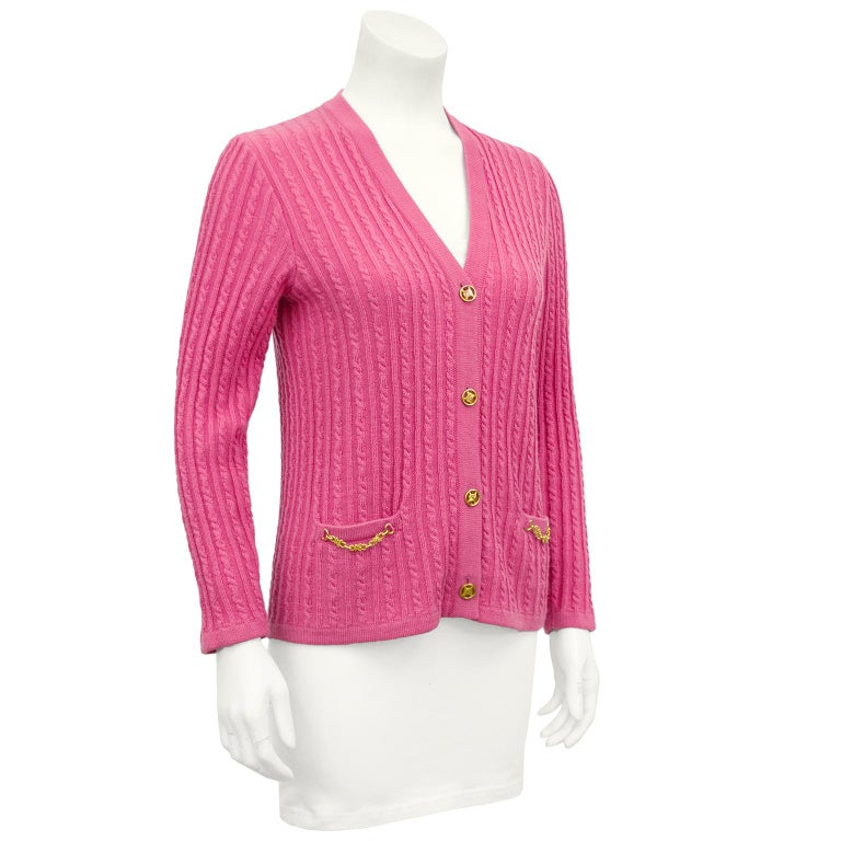 Pretty in pink 1970's Celine cardigan. Wool cable knit with gold Celine logo gold buttons and gold chain details at flat pockets. In excellent vintage condition, marked FR 38. Matches our 1970's Celine Pink Wool Pleated Skirt.