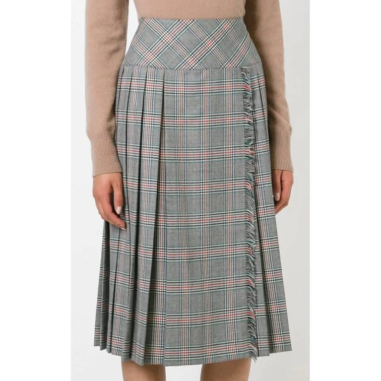 Céline midi skirt with gray, black and red Prince of Wales pattern, with high waist, side and back folds, lacing with golden buttons and fringed hem.  Years: 70s  Made in France  Size: 38 FR  Linear measures  Height: 70 cm Waist: 35 cm Hips: 45 cm