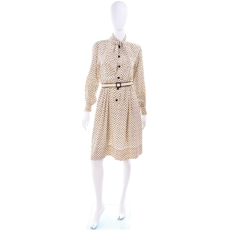 This is a lovely 1970's vintage Chanel silk dress is in a pretty black and light cream tulip floral print. This Chanel Créations long sleeve day dress has an attached scarf at the neckline that can be knotted or tied in a bow, and there are buttons
