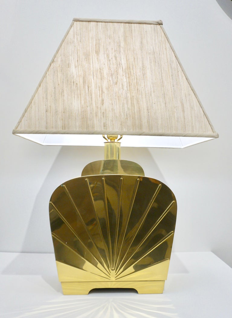 A very chic vintage pair of glamorous American Hollywood Regency table lamps. Exquisite high quality of execution in handcrafted shiny gold heavy solid brass, the streamline organic shape is elegantly decorated with an Art Deco style cast decor in