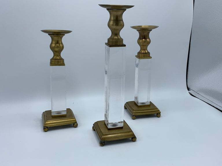 Listed is a gorgeous, set of three, 1970s Charles Hollis Jones style Lucite and brass candlesticks. Large(x1); 3.5in D x 3.5in W x 12.5in H. Small(x2); 3.5in D x 3.5in W x 10.25in H. Each Lucite block is 1.5in thick. Heavy, 5.5lbs for the entire set.
