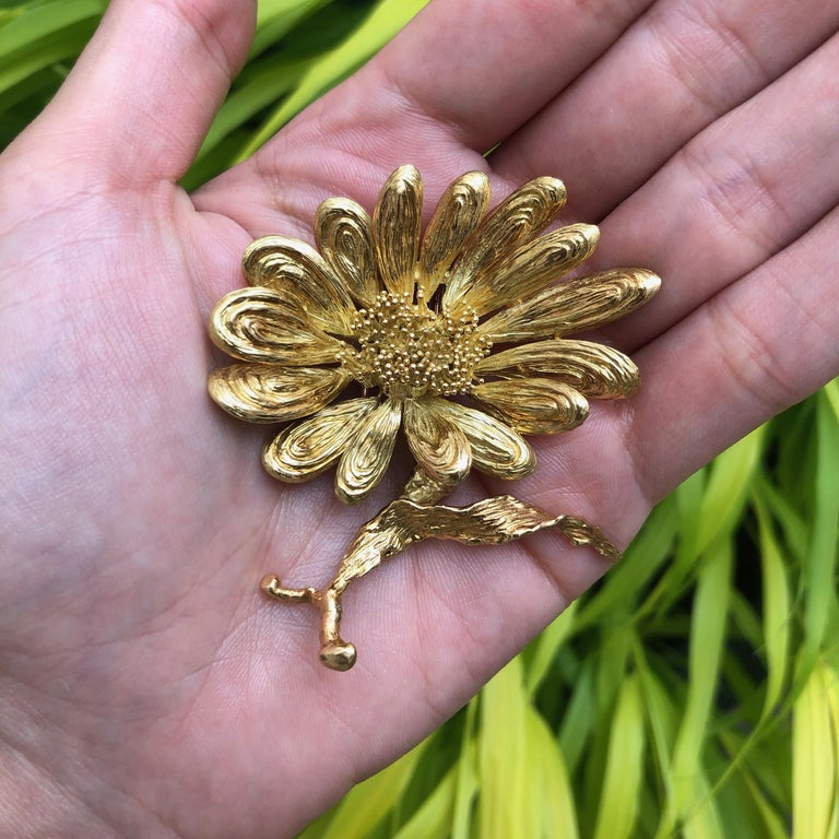 An 18 karat textured gold floral motif brooch, by Chaumet, 1970s.   The brooch is stamped Chaumet paris, french eagle mark, stamped with makers mark.
