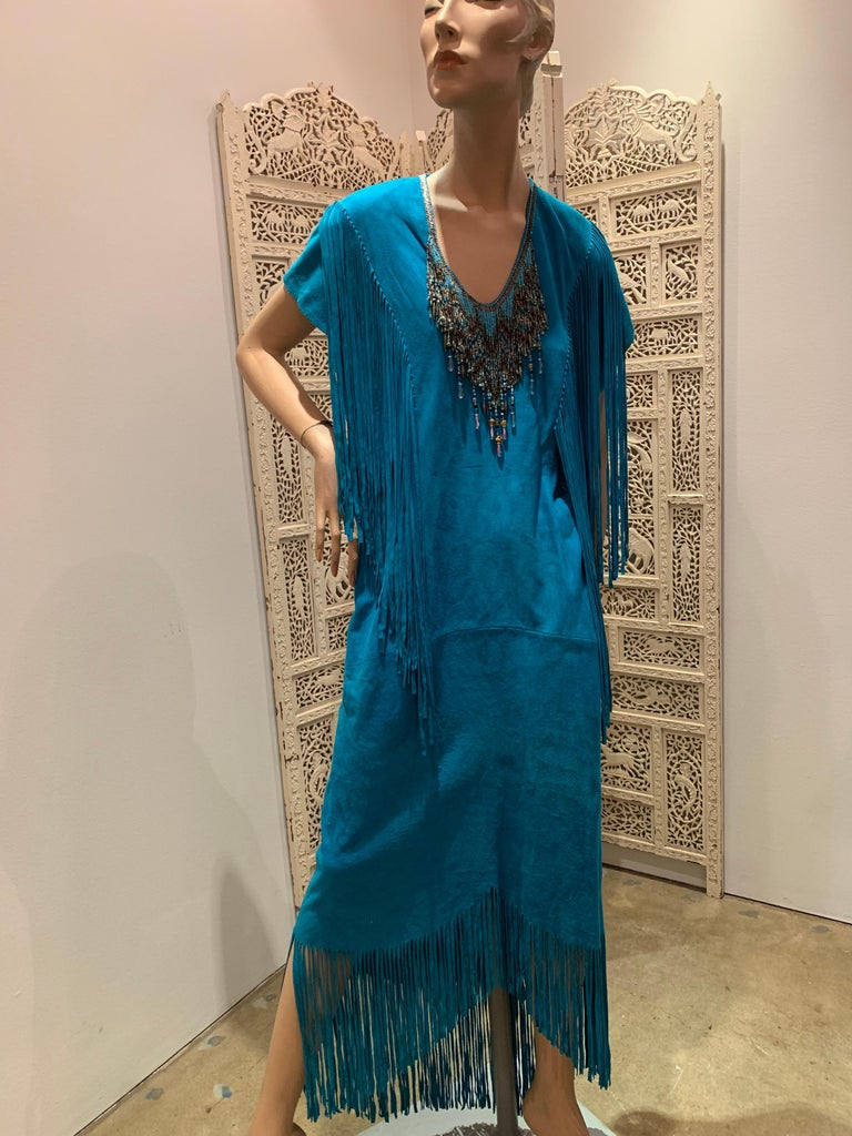 A sexy 1970s Chic Skins of California turquoise doeskin suede caftan with cut suede fringe at hem and shoulders and heavy glass beaded Native American-inspired fringe at neckline.