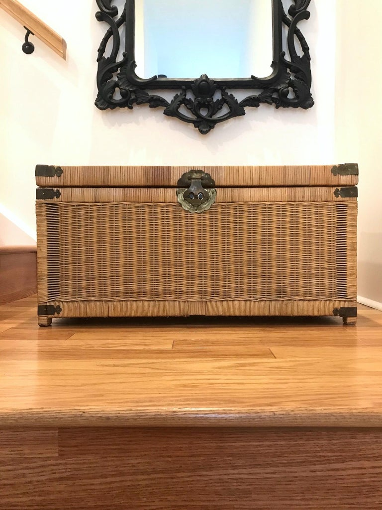 Vintage Asian storage chest and trunk in natural handwoven wicker. Campaign style design featuring a wood frame wrapped in woven wicker with brass metal hardware. Hammered brass metal accents and hardware with Asian motifs throughout. Lid opens to
