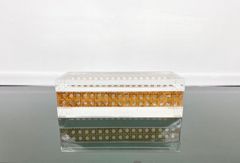 Stunning Mid-Century Modernist Lucite decorative box designed for Christian Dior Home Collection in 1970s. Large rectangular shape with real rattan canework embedded in the crystal clear Lucite. Great accessory for any modern interior.