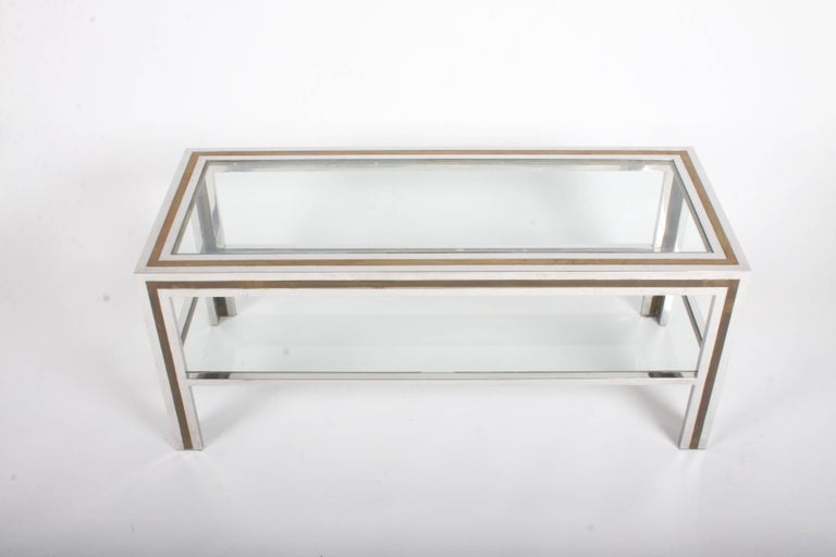 Vintage Italian 1970s chrome and brass two-tier coffee table. Minor scuffs to chrome and patina to brass, glass has light scratches. The two tone frame reminds me of Gucci's picture frames from the late 1970s and early 1980s. Lower shelf is 8.75