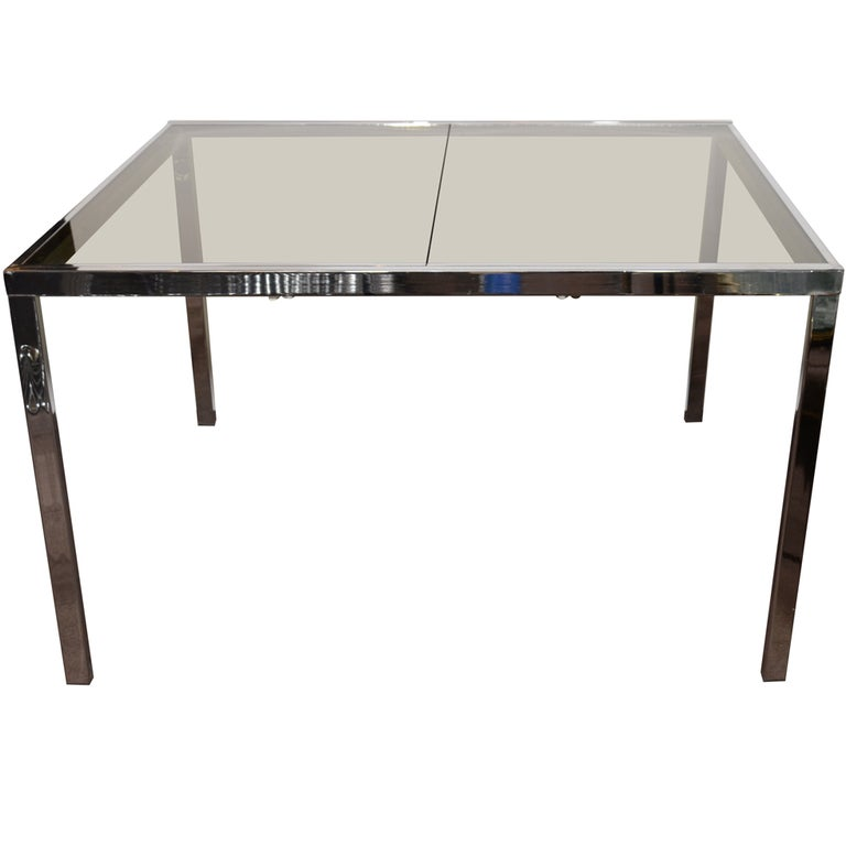 Milo Baughman for Design Institute of America, Mid-Century Modern dining table with streamline design in chrome and with smoked glass top and inset leaf. Features built-in smoked glass extension which raises flush to the table by unlocking underside
