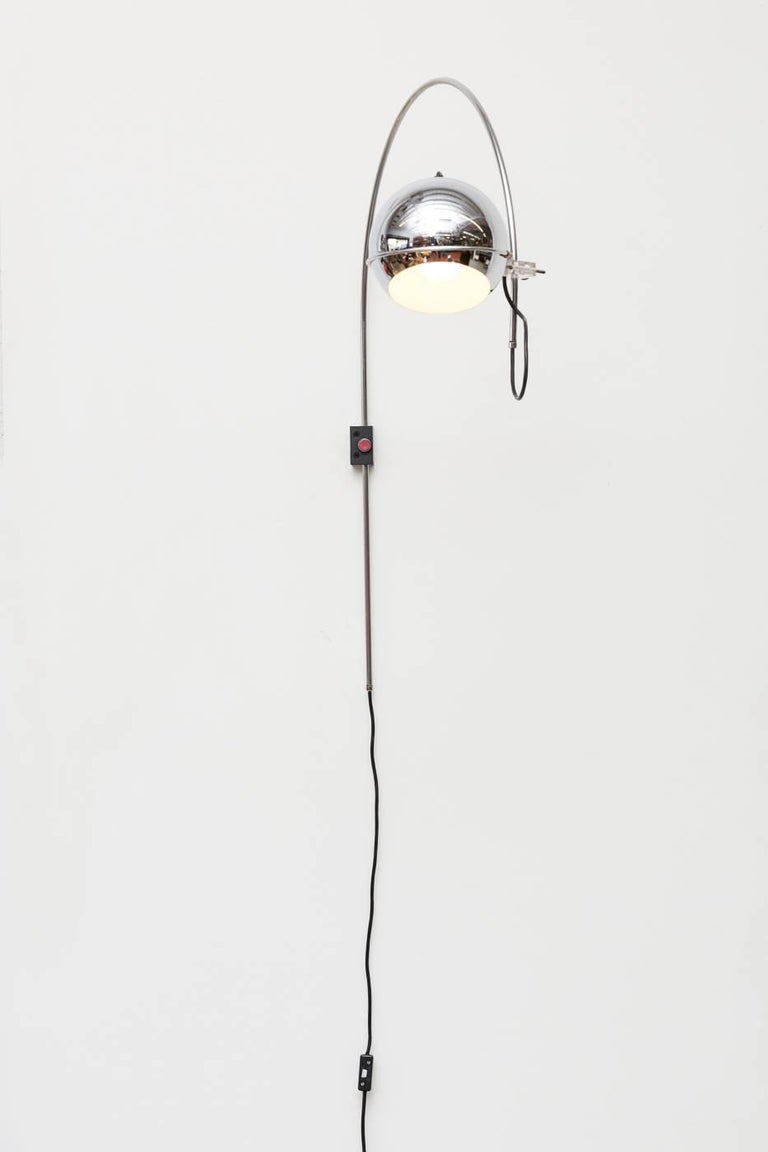 1970s midcentury chrome Gepo arc wall lamp with acrylic hardware and black rectangular mount. Good original condition with visible wear consistent with its age and usage.