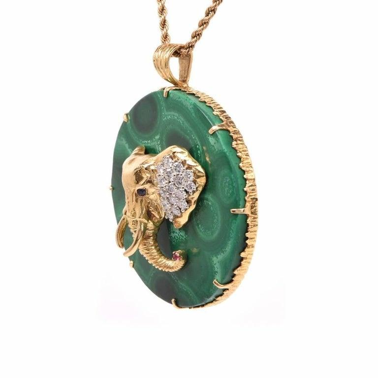 This vintage  circular pendant circa 1970's pendant  is made of solid 18k gold frame with malachite Stone. Enriched with an elephant head with pave set diamond ears, sapphire eyes and a ruby on her trunk.  Elongated yellow gold prongs and a wide