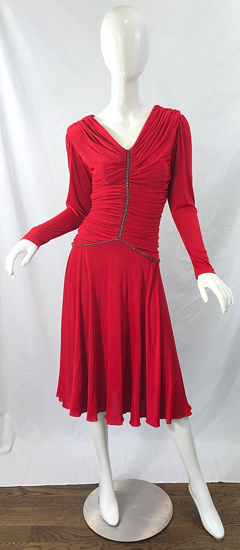 Beautiful late 1970s CLARALUNA ORGINIAL lipstick red rhinestone encrusted long sleeve vintage jersey dress ! Features a tailored flattering ruched bodice, with rhinestones down the front center and waistband. Soft rayon stretches to fit. Hidden